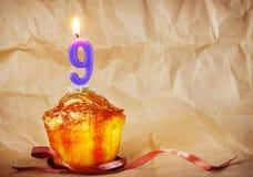 Torta de cumpleaños con la vela ardiente como número nueve Foto de archivo libre de regalías