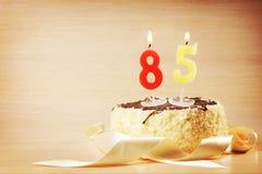 Torta de cumpleaños con la vela ardiente como número ochenta y cinco Imagen de archivo libre de regalías