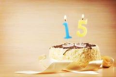Torta de cumpleaños con la vela ardiente como número quince Fotografía de archivo