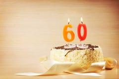 Torta de cumpleaños con la vela ardiente como número sesenta Fotografía de archivo
