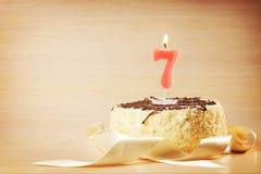 Torta de cumpleaños con la vela ardiente como número siete Fotografía de archivo libre de regalías
