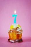 Torta de cumpleaños con la vela ardiente como número siete Foto de archivo