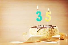 Torta de cumpleaños con la vela ardiente como número treinta y cinco Imagen de archivo libre de regalías