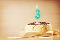 Torta de cumpleaños con la vela ardiente como número tres Fotografía de archivo