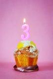 Torta de cumpleaños con la vela ardiente como número tres Imágenes de archivo libres de regalías