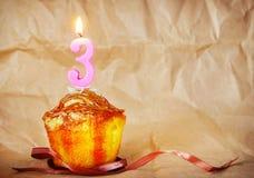 Torta de cumpleaños con la vela ardiente como número tres Imagen de archivo libre de regalías