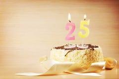 Torta de cumpleaños con la vela ardiente como número veinticinco Fotografía de archivo