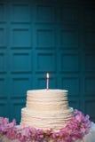 Torta de cumpleaños con la vela ardiente en fondo azul; Fotos de archivo