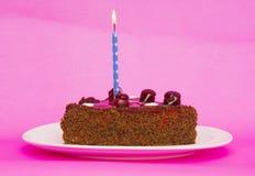Torta de cumpleaños con las velas en fondo rosado Fotos de archivo libres de regalías