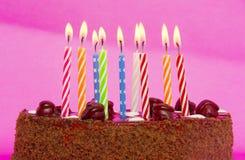 Torta de cumpleaños con las velas en fondo rosado Imágenes de archivo libres de regalías