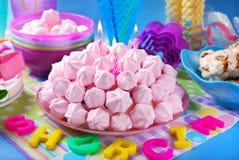 Torta de cumpleaños con los merengues y las velas rosados Fotos de archivo