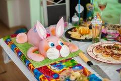 Torta de cumpleaños de los niños en el partido rodeado por los presentes y el sombrero del partido Fotografía de archivo