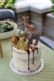 Torta de cumpleaños del niño con los animales africanos del juguete que rematan con la salsa de chocolate lloviznada en el icingw imagen de archivo