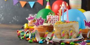 Torta de cumpleaños y diversos accesorios para el día de fiesta Foto de archivo