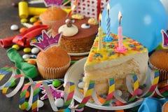 Torta de cumpleaños y diversos accesorios para el día de fiesta Imagen de archivo