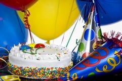 Torta de cumpleaños, sombreros del partido y globos Fotos de archivo libres de regalías
