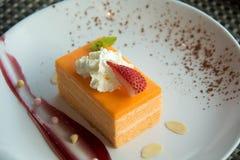 Torta de esponja anaranjada en una placa blanca imagen de archivo