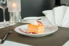 Torta de esponja anaranjada en una placa blanca fotografía de archivo