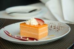 Torta de esponja anaranjada en una placa blanca imagenes de archivo