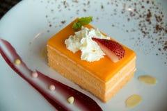 Torta de esponja anaranjada en una placa blanca foto de archivo libre de regalías