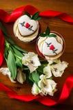 Torta de la bagatela con una nota con una predicción y flores en una tabla de madera foto de archivo