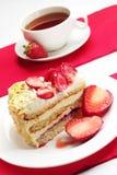 Torta de la fresa y taza de té Fotografía de archivo libre de regalías