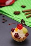 Torta de la fruta con crema azotada y una cereza en fondo gris Foto de archivo libre de regalías