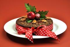 Torta de la fruta de la Navidad con acebo y la cinta Imagenes de archivo
