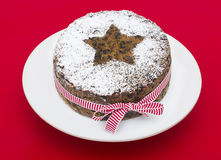 Torta de la fruta de la Navidad en un fondo rojo Imagen de archivo