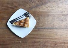torta de la macadamia en la placa blanca con las bifurcaciones en la tabla de madera imagen de archivo