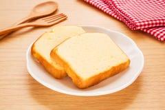 Torta de la mantequilla cortada en la placa Imagen de archivo libre de regalías
