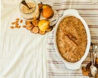 Torta de la migaja de la harina de avena de la pera en plato que cuece azul Mantel de lino foto de archivo