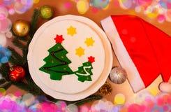 Torta de la Navidad con las ramas del abeto, las decoraciones y el sombrero de santa Fotos de archivo libres de regalías