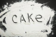 Torta de la palabra escrita en la harina blanca, fondo negro fotografía de archivo