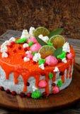 Torta de la semilla de amapola cubierta con el esmalte rojo del espejo y adornada con el merengue, rebanadas de la cal, hojas del Foto de archivo