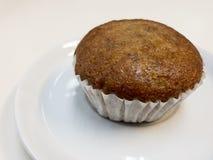 Torta de la taza del plátano en el plato blanco Foto de archivo