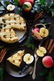 A torta de maçã americana da tradição com maçãs, mirtilo e canela decorou as folhas da maçã no fundo de madeira escuro Imagem de Stock Royalty Free