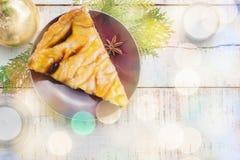 Torta de maçã do Natal na placa com velas e brunche brancos da árvore Imagens de Stock Royalty Free