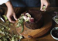 Torta de Man Decorating Chocolate del panadero con las flores foto de archivo