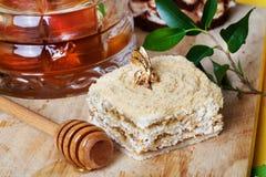 Torta de miel y una cuchara especial en vida inmóvil con Imágenes de archivo libres de regalías