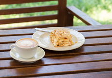 Torta de Napoleon, café del capuchino en una tabla de madera en el mirador en el café, en el jardín Fotos de archivo libres de regalías