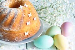 Torta de Pascua con las mariposas y los huevos del caramelo en fondo floral del blanco del extracto de la primavera Foto de archivo