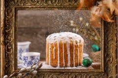Torta de Pascua en el esmalte contra la perspectiva del marco antiguo Huevos del juego de té y de codornices en el fondo Un marco Foto de archivo