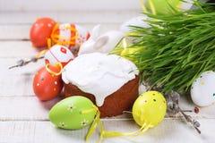 Torta de Pascua, huevos de Pascua coloridos, hierba en el backgro de madera blanco imagenes de archivo