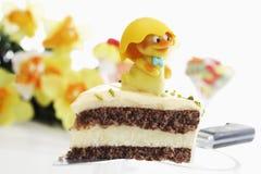 Torta de Pascua, pedazo de torta del mazapán con el pistacho y estatuilla del polluelo fotos de archivo libres de regalías