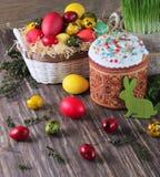 Torta de Pascua y huevos coloridos en un fondo de madera Fotos de archivo