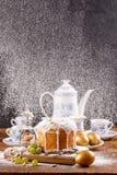 Torta de Pascua y huevos de oro con una tetera y las tazas de té Tarjeta hermosa para Pascua El polvo del azúcar se vierte sobre  Imágenes de archivo libres de regalías
