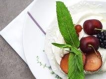 Torta de Pavlova con las bayas, la cereza, la zarzamora, la fresa y la menta imagen de archivo libre de regalías