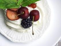 Torta de Pavlova con las bayas, la cereza, la zarzamora, la fresa y la menta imágenes de archivo libres de regalías