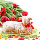 Torta del cordero de Pascua y tulipanes rojos Fotos de archivo
